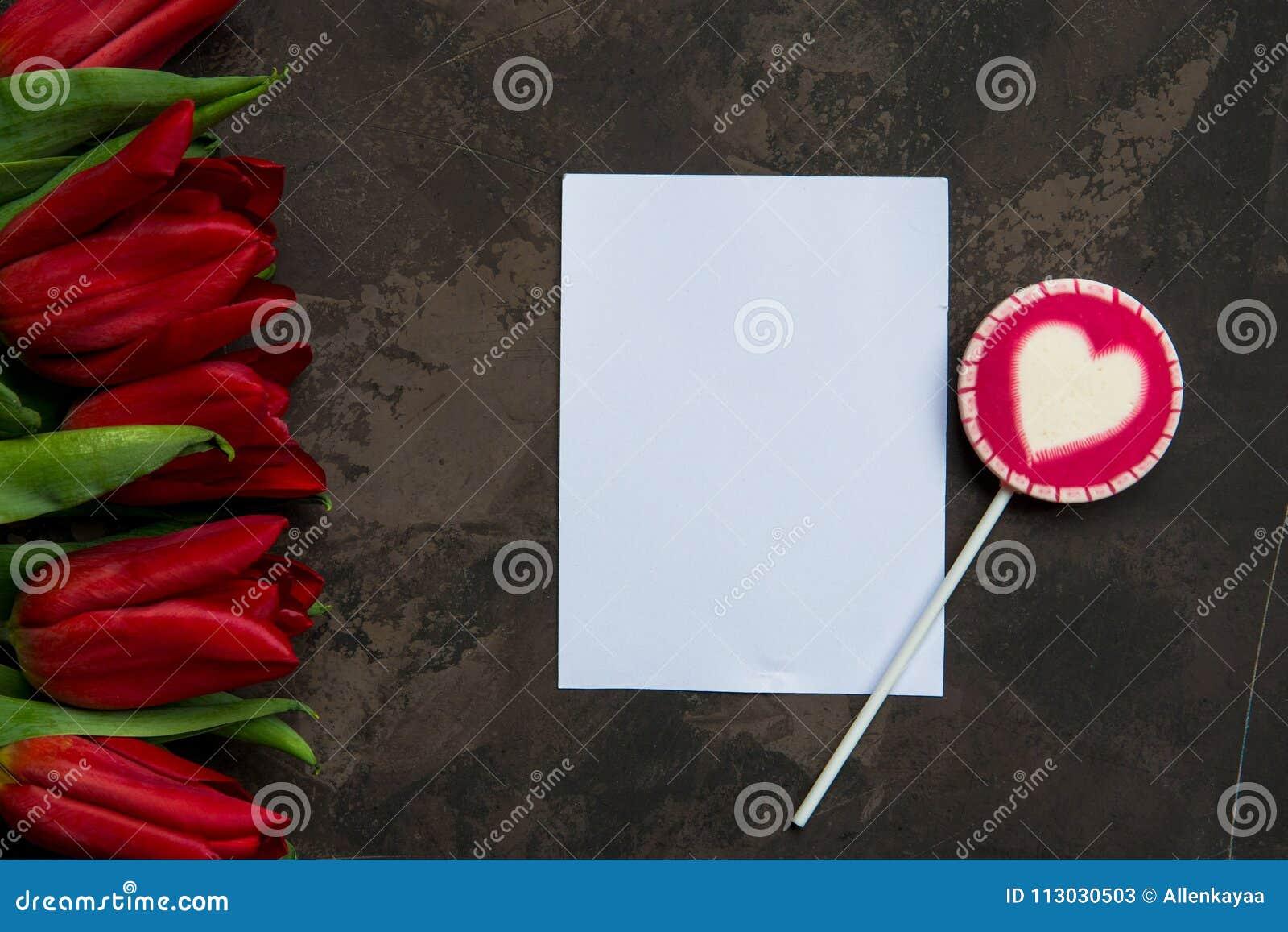 Tulipanes y piruleta rojos con el espacio de la copia para su texto