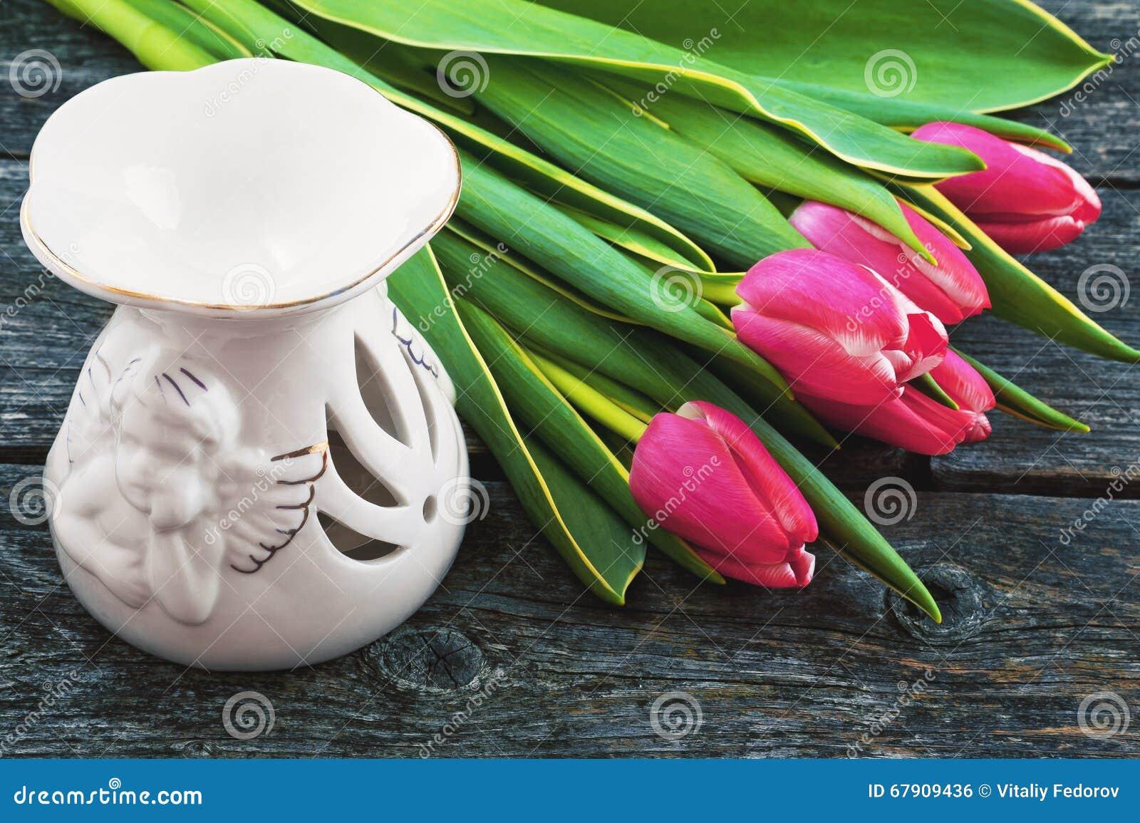 Lampada Fiore Tulipano : Tulipani rosa e una lampada aromatica su un fondo di legno