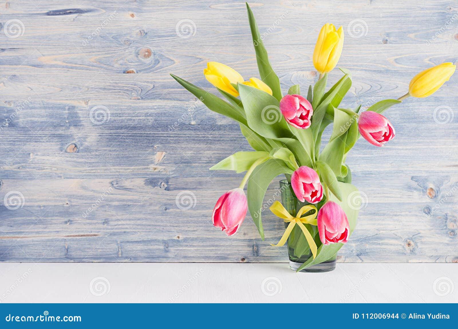 Tulipes jaunes et rouges dans le vase sur le conseil en bois chic minable bleu Fond de ressort d avril, intérieur de maison, déco