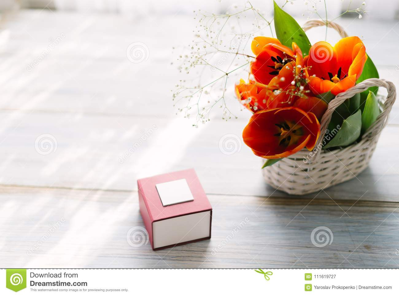 Tulips in a basket on a white wooden background