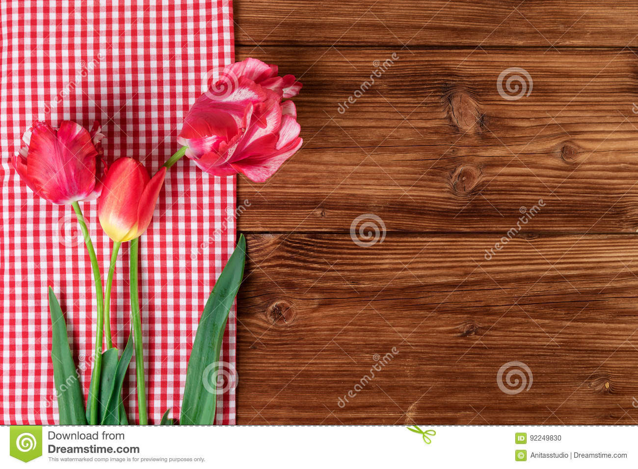 Tulips with red checkered tablecloth on country wooden background. Top view, text space