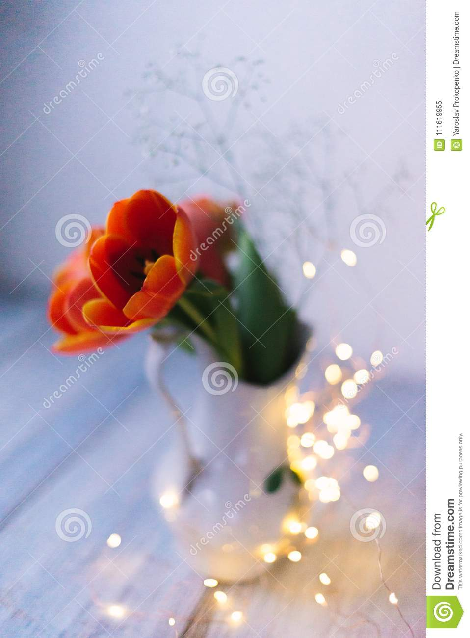 Tulips in a vase on a wooden background