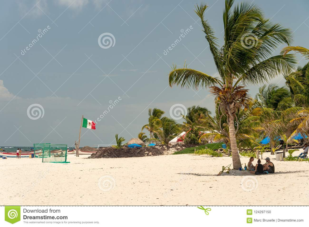 Playa Tulum beach with palm trees and mexican flag.
