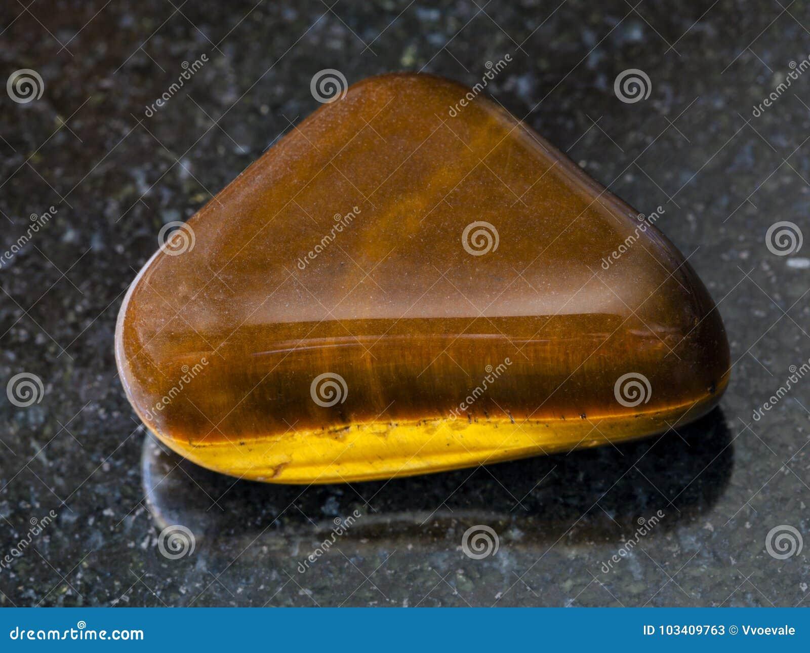 tumbled tiger eye gem stone on dark background stock image image