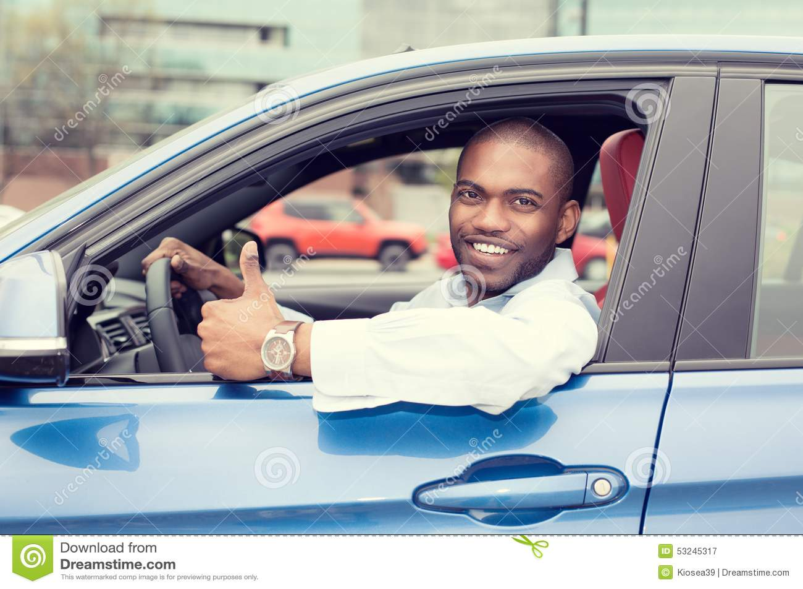 Tummar den lyckliga le visningen för manchaufför upp körning av den blåa bilen för sporten