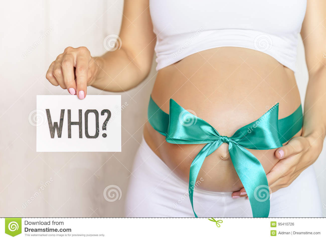 Tummy with green ribbon and bow of pregnant caucasian woman which is holding question