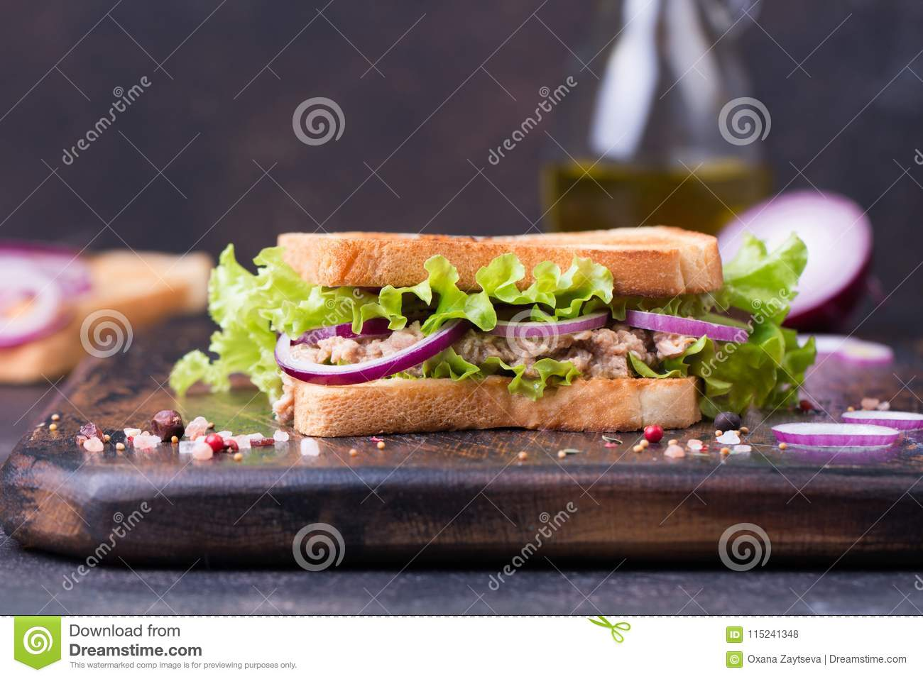 Tuna fish sandwich with onion, lettuce and olive oil on a wooden board.