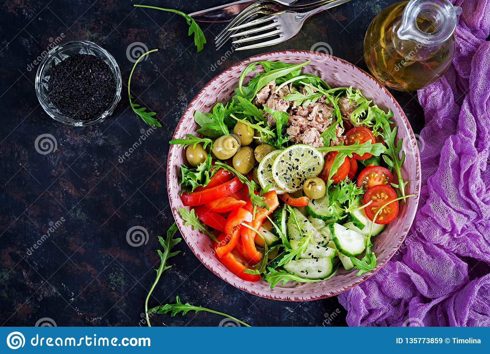 Tuna salad with tomatoes, olives, cucumber, sweet pepper and arugula