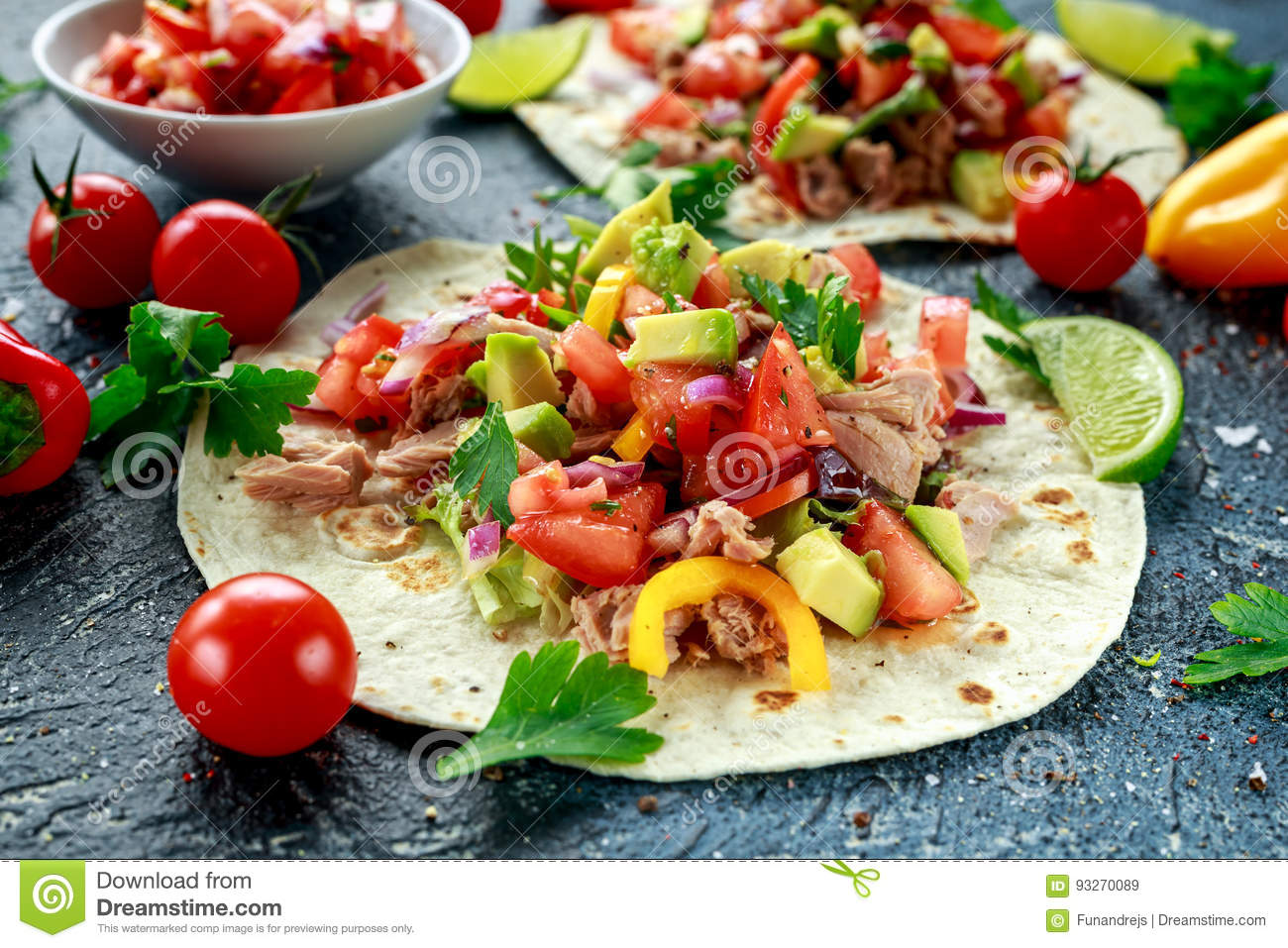 Tuna Tortilla with avocado, fresh salsa, limes, greens, parsley, tomatoes, red yellow pepper. colorful vegetable