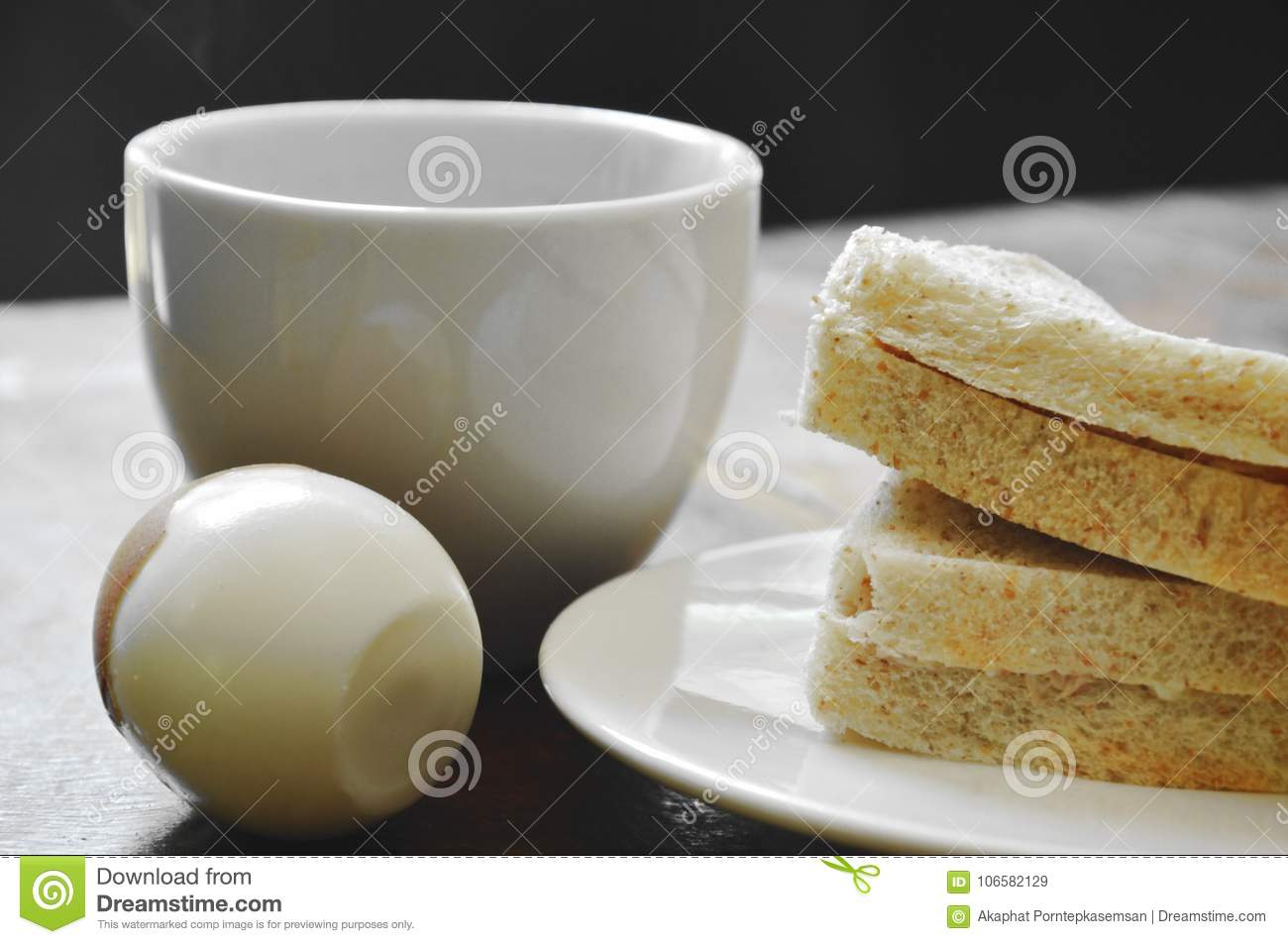 Tuna whole wheat sandwich on plate and boiled egg eat couple with black coffee cup