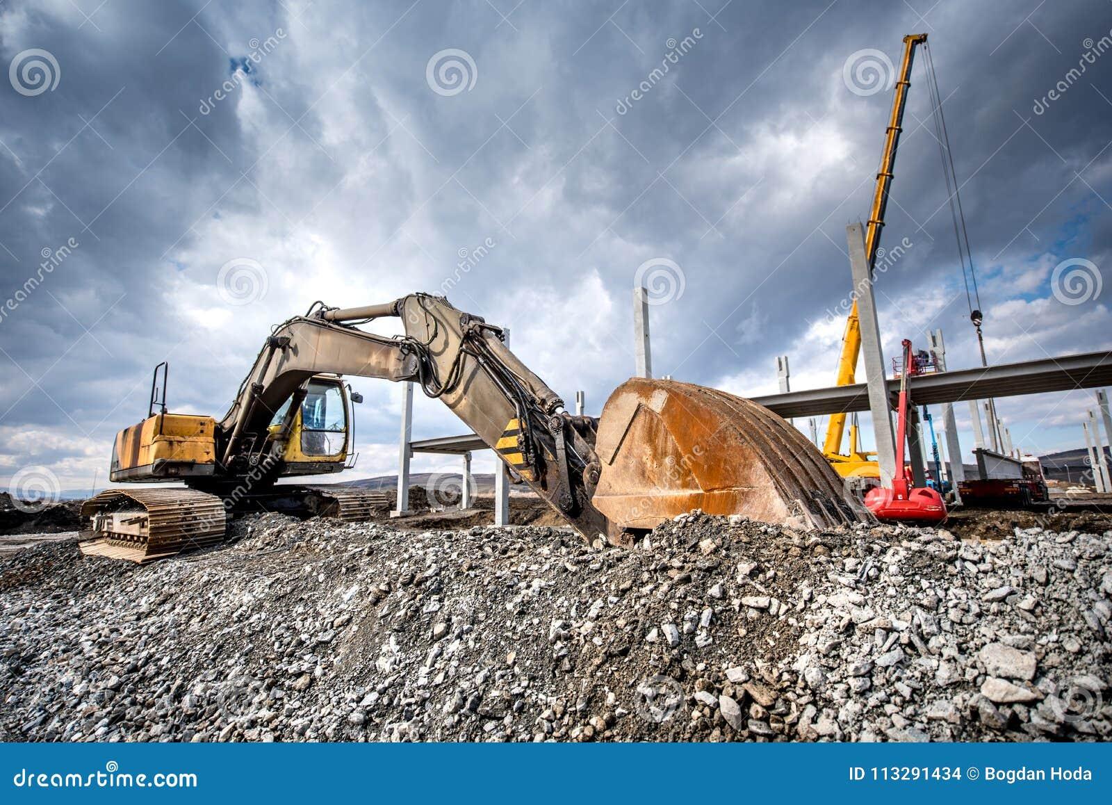 Tungt industriellt grävskopapäfyllningsgrus på konstruktionsplats Detaljer av byggnadsplatsen