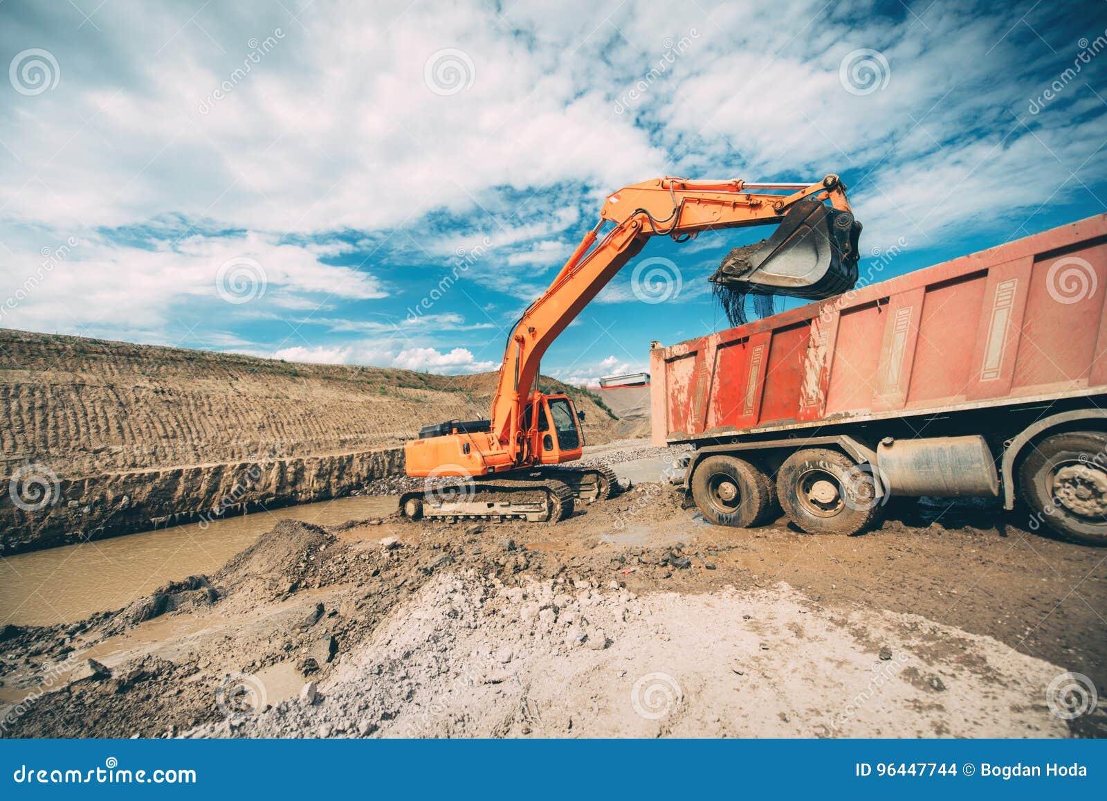 Tungt maskineri, detaljer av grävskopabyggnadshuvudvägen och päfyllningsdumper