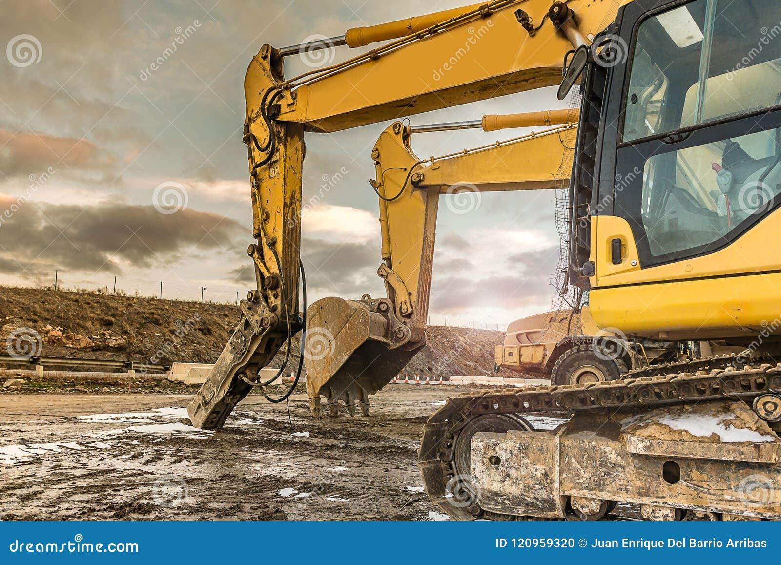 Tungt maskineri i en hård dag av arbete i konstruktionen av en väg