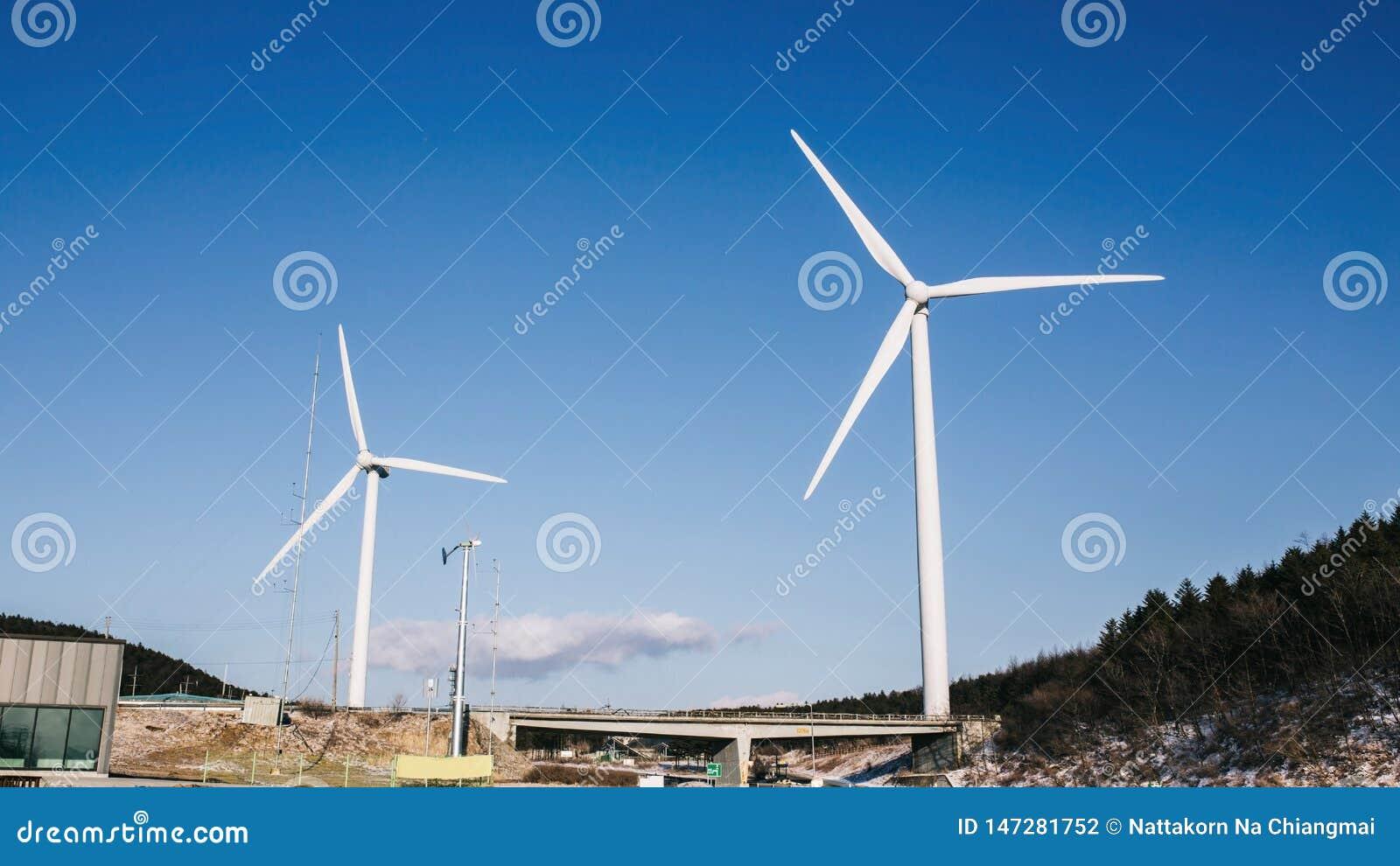 Turbina de viento en campo y prado en la montaña con el cielo azul de la belleza y el fondo nublado