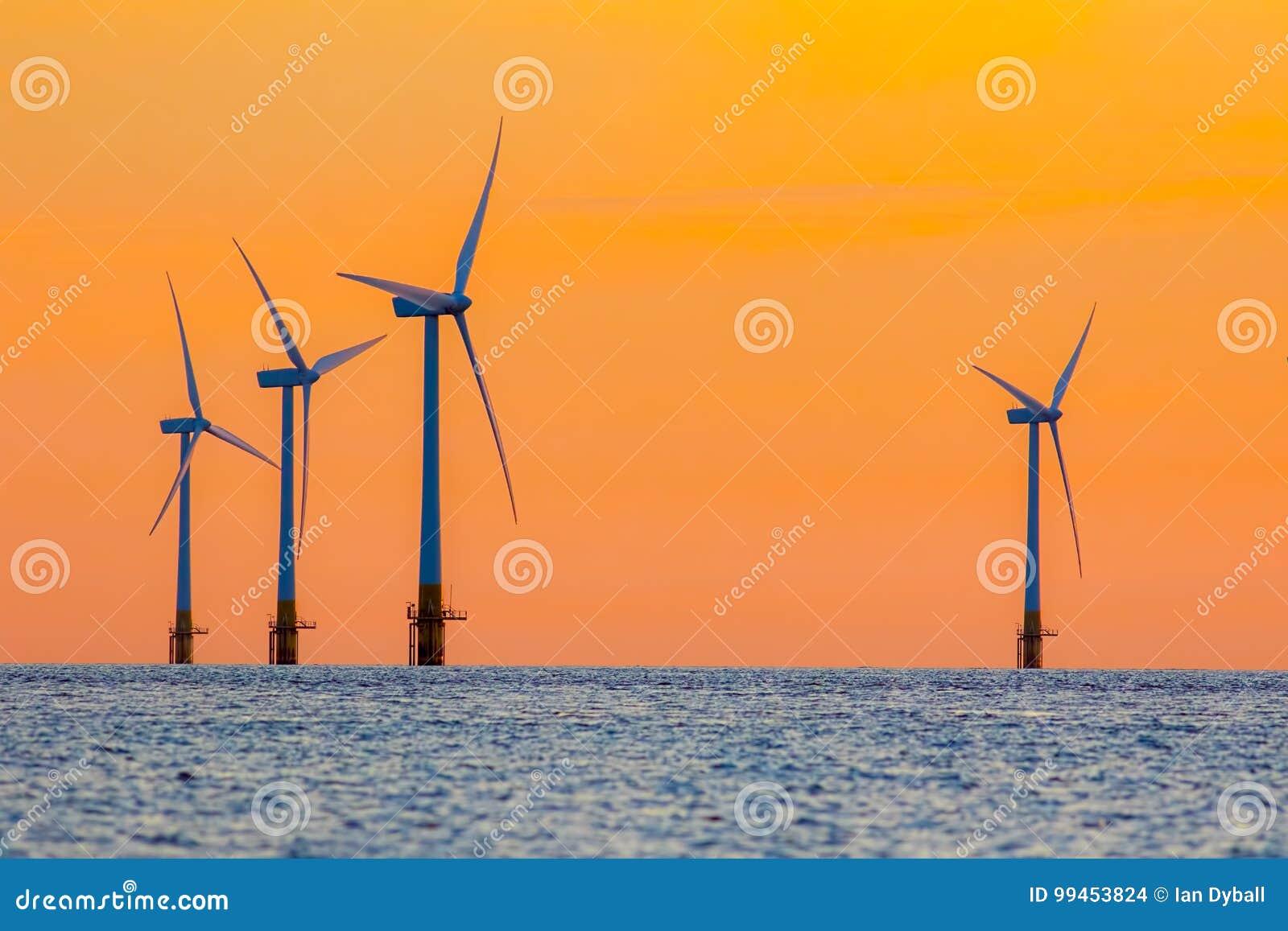 Turbinas da energia da exploração agrícola de vento a pouca distância do mar no alvorecer Surreal mas natural