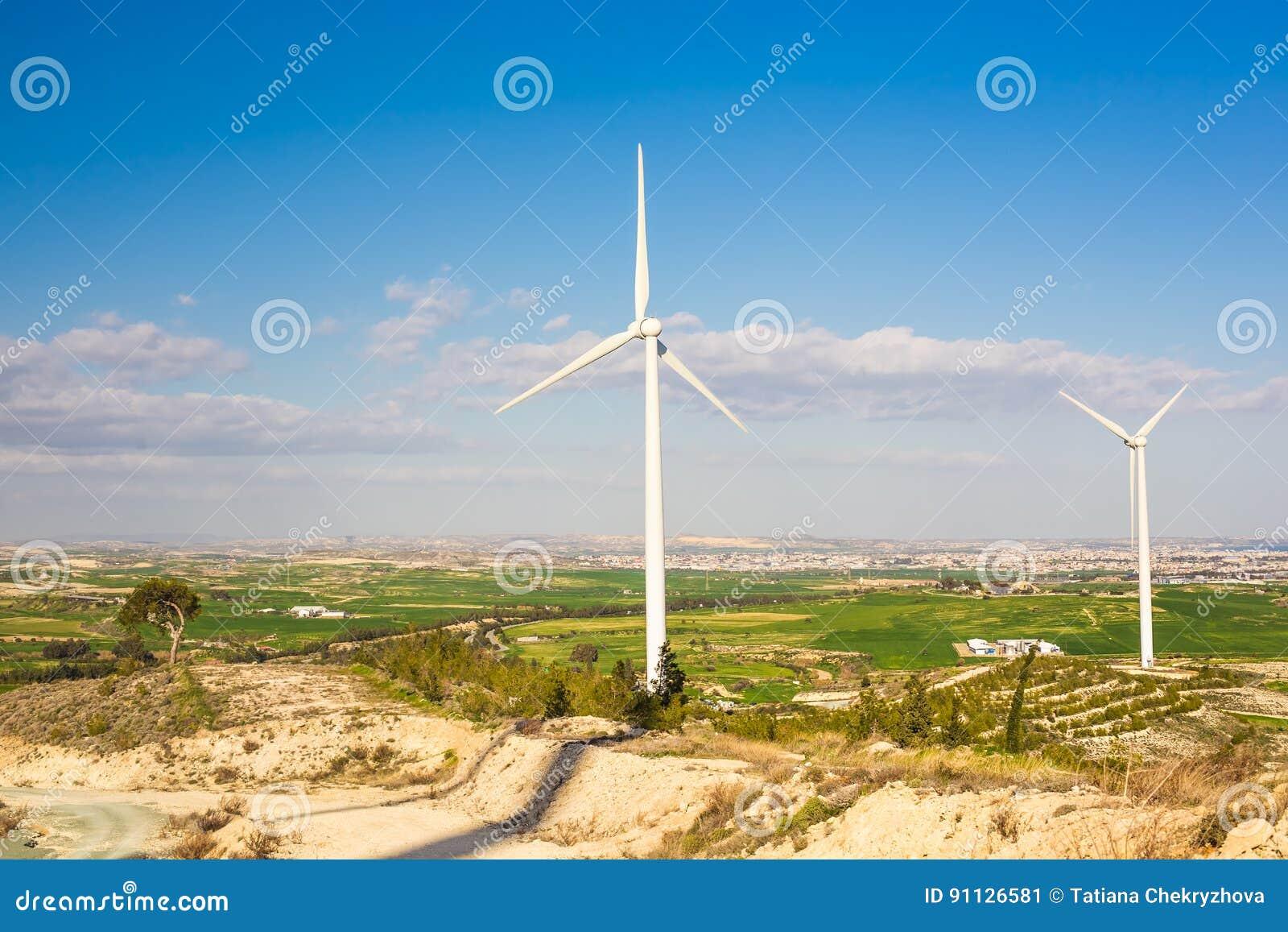 Turbinas de viento que generan la electricidad con el cielo azul - concepto del ahorro de energía