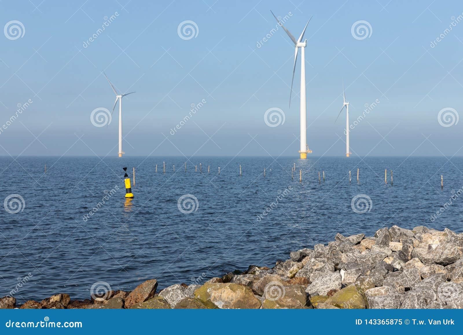 Turbinas eólicas a pouca distância do mar perto da costa holandesa com boia