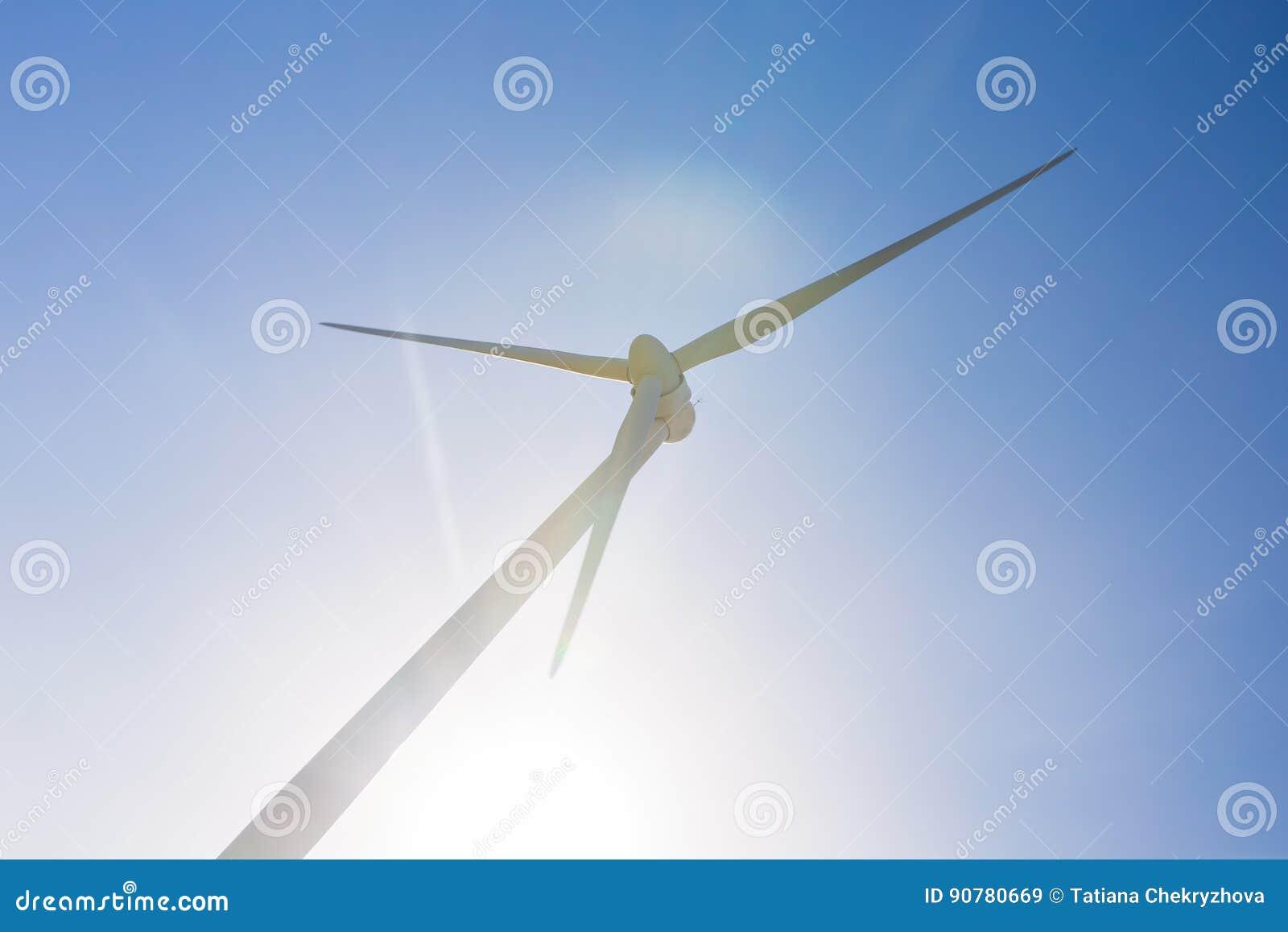 Turbines de vent produisant de l électricité avec le ciel bleu - concept d économies d énergie