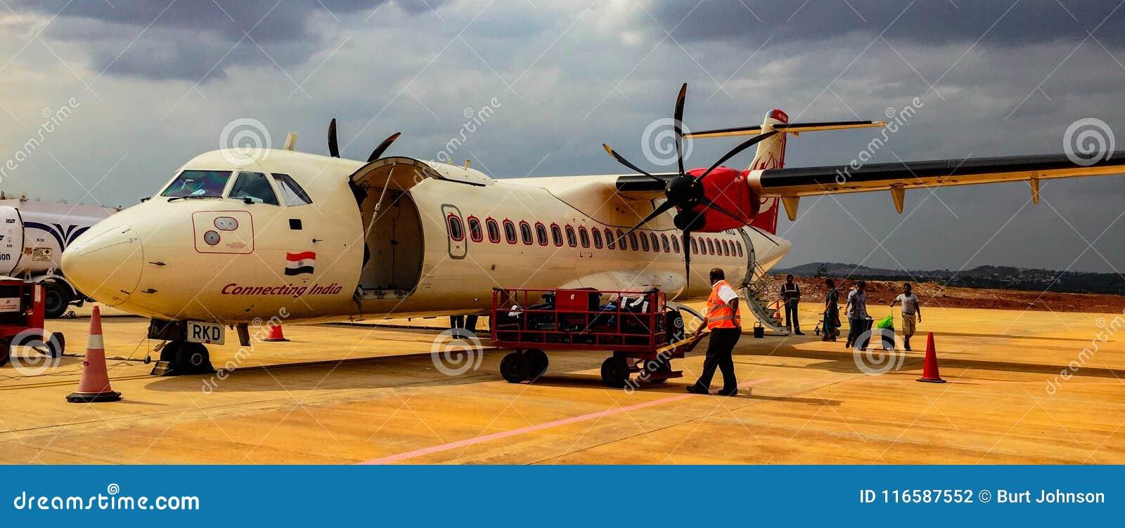 Turboladdarestöttaflygplanet sitter på grov asfaltbeläggningpäfyllningspassagerare och luggag