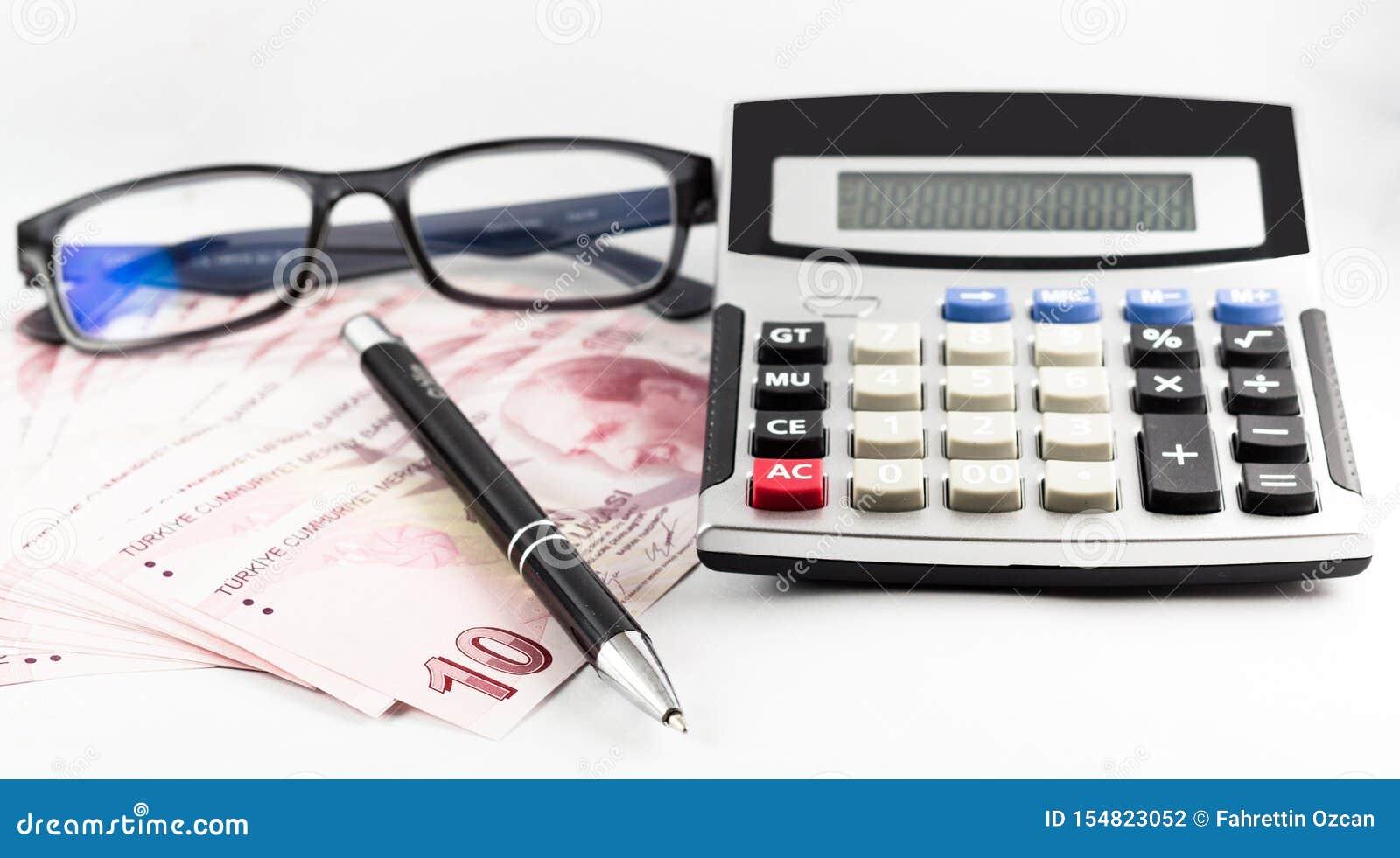 Tureccy banknoty, szkła, pióro i kalkulator na białym tle,
