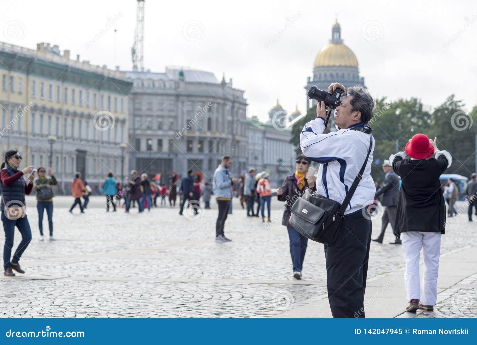 Turist- asiatiska utseendemässiga fotografier för man på kameradragningar på slottfyrkanten av St Petersburg, Ryssland, September