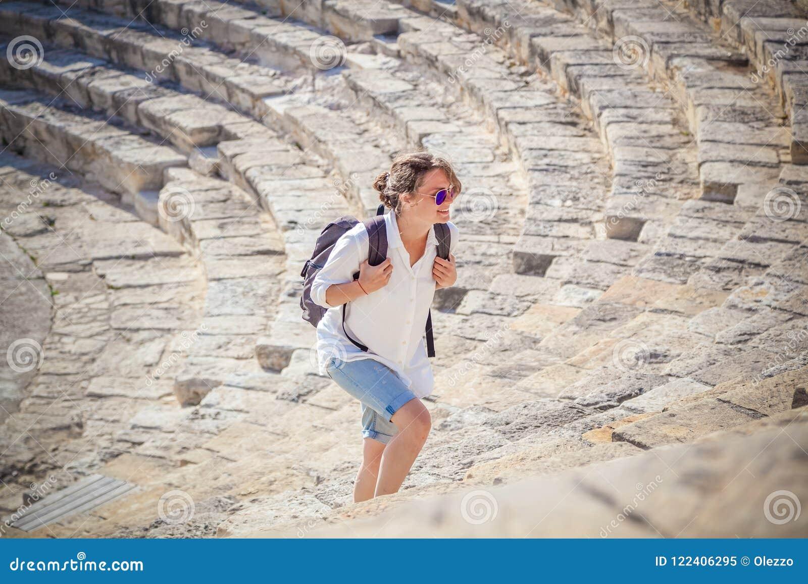 Turist för ung kvinna med en ryggsäck på bakgrunden av sten