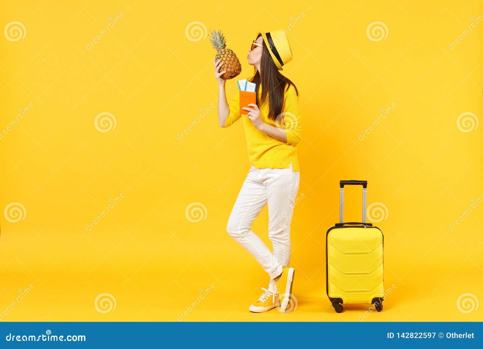 Turist- kvinna för mjuk handelsresande i biljetter för hattinnehavpass som kysser ananasfrukt som isoleras på den gula apelsinen