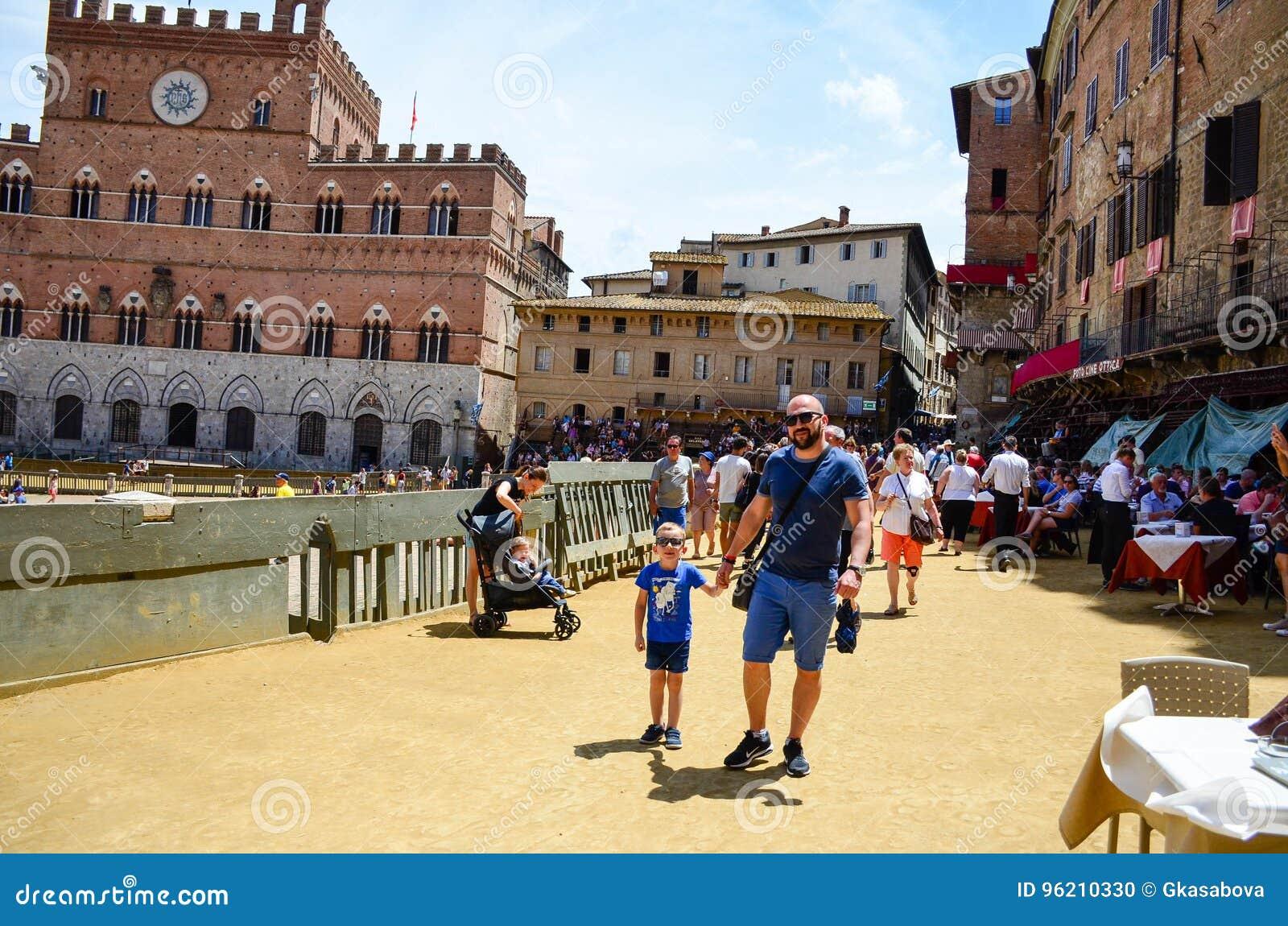 Turist nära Palazzo Publico i det Piazza del Campo stadshuset av Siena, Tuscany, Italien