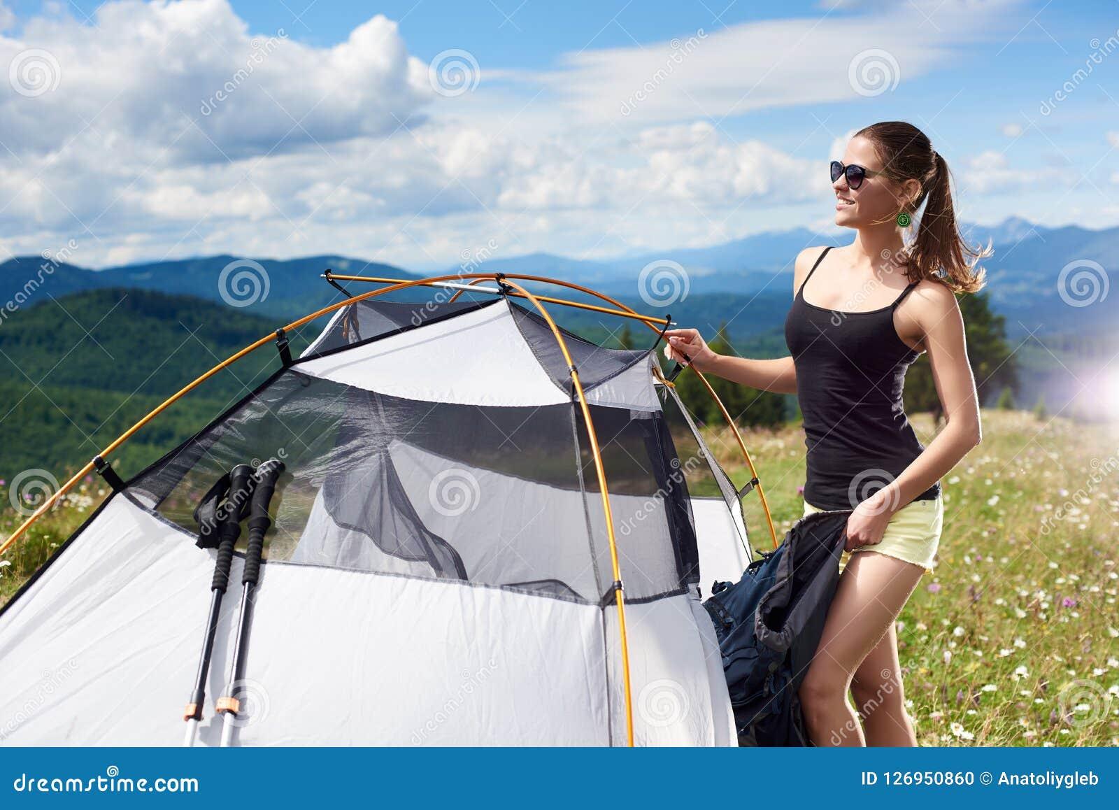Turist- near fotvandra för kvinna i bergslingan som tycker om solig morgon för sommar i berg, tältet