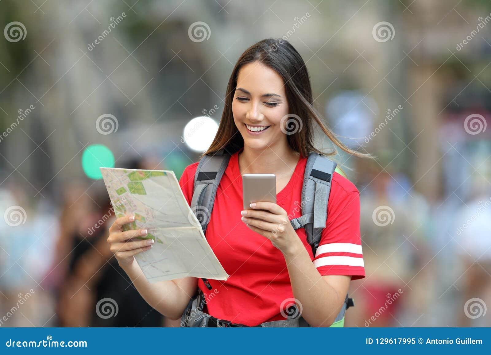 Turista adolescente que procura o lugar em linha na rua