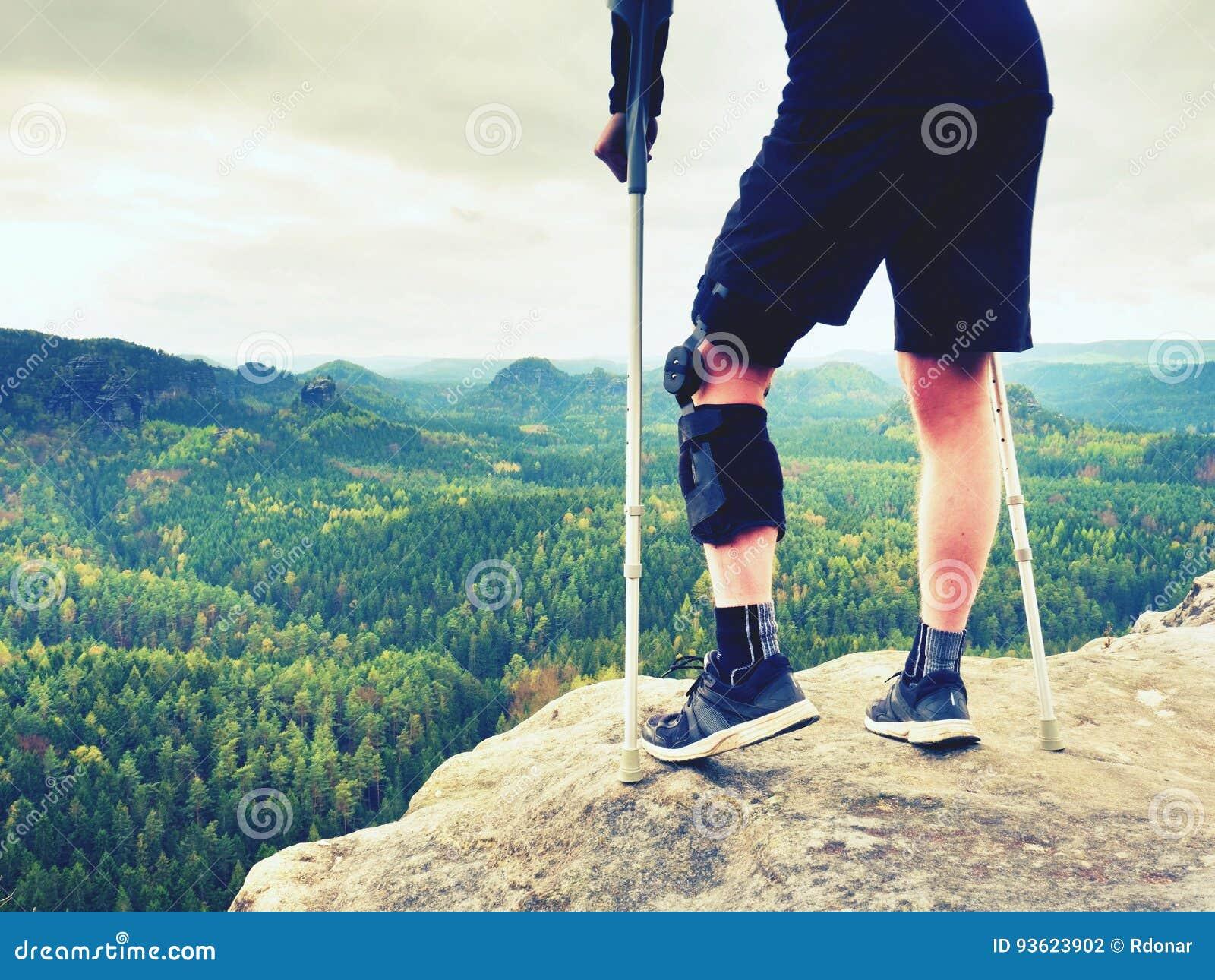 Turista cansado de dano com muletas da medicina O homem com pé quebrado na cinta de joelho caracteriza o descanso na cimeira roch
