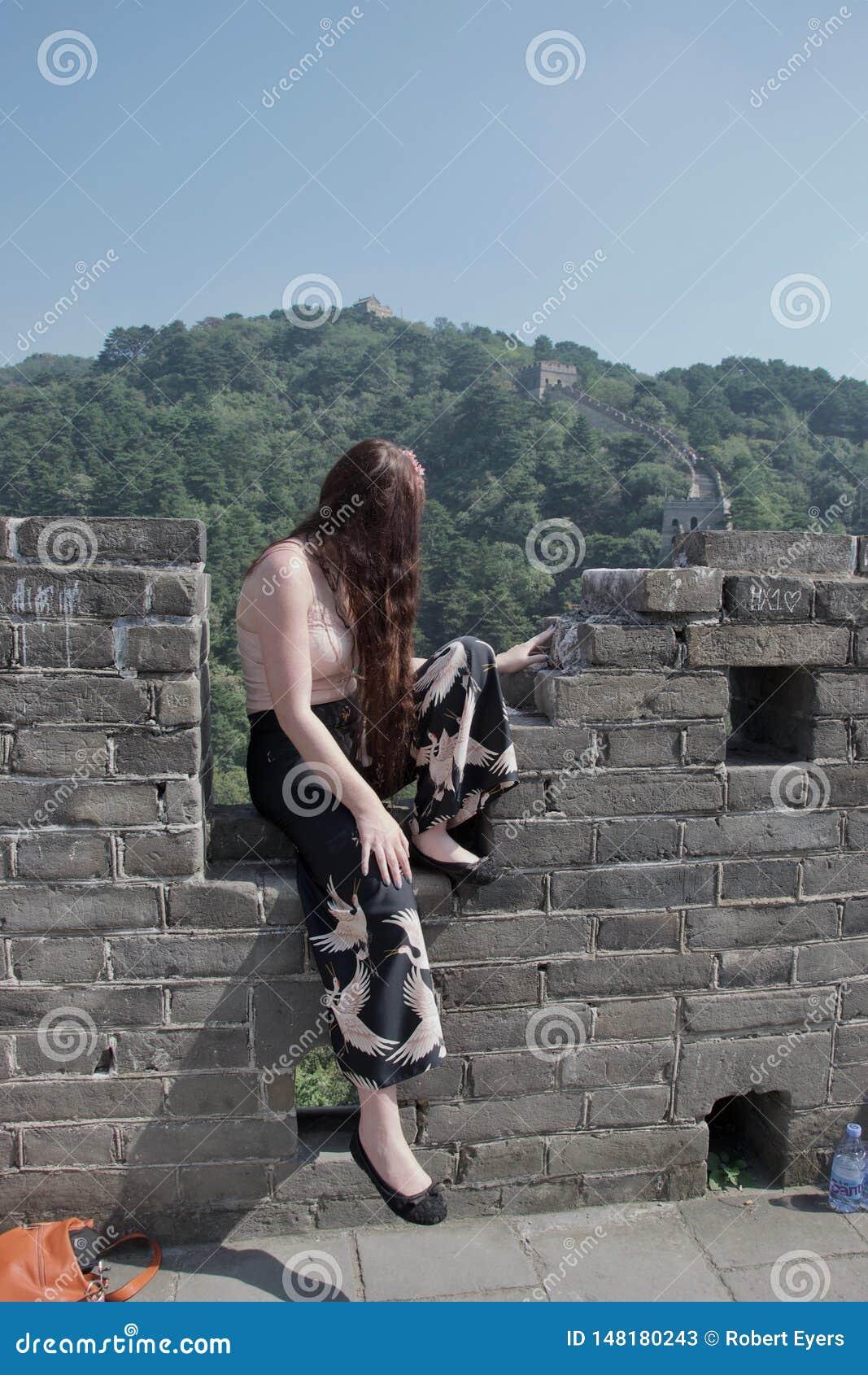 Turista cauc?sico femenino de moda que presenta en la Gran Muralla de China