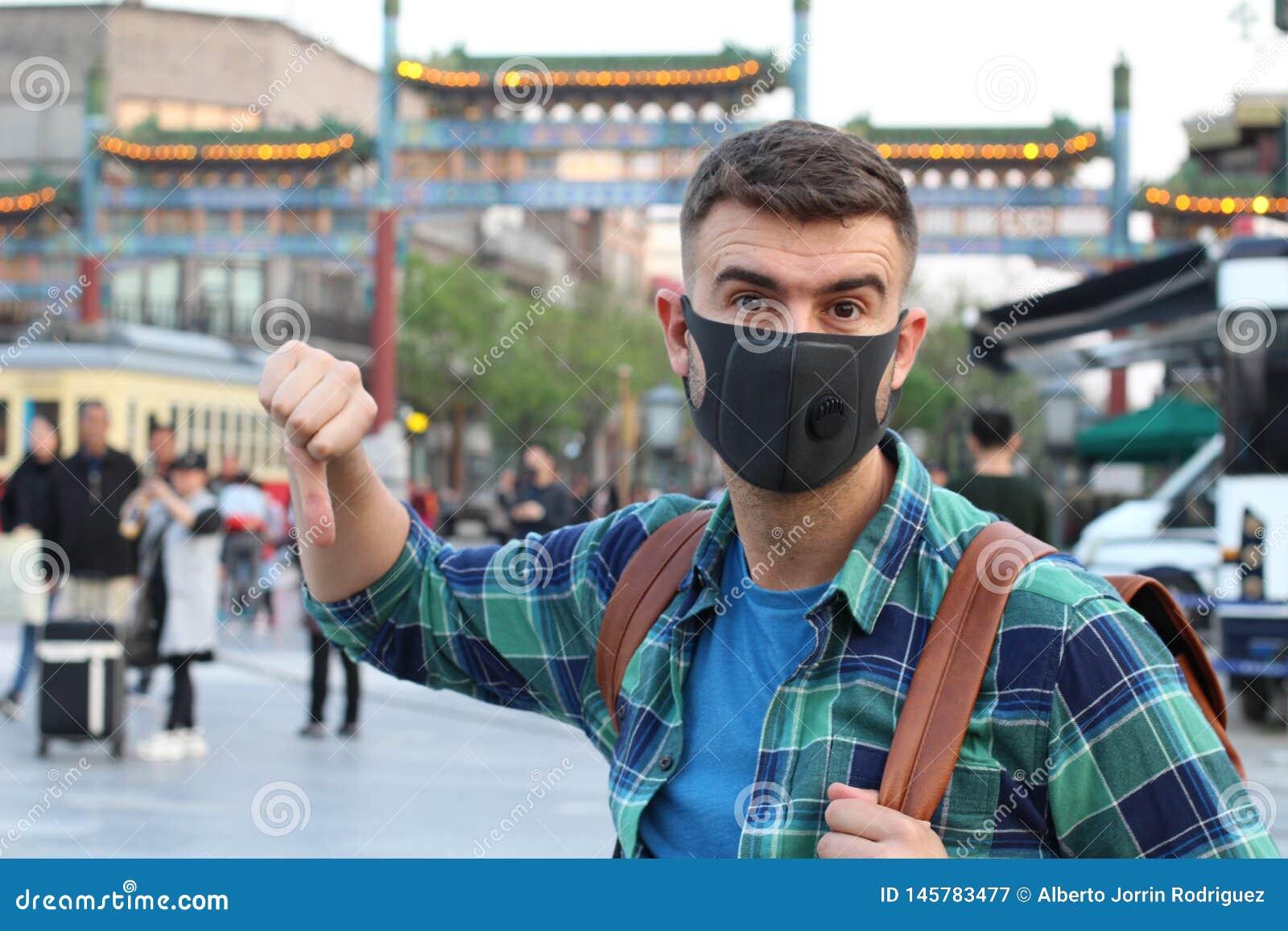 Turista caucasico che utilizza la maschera di inquinamento in Asia
