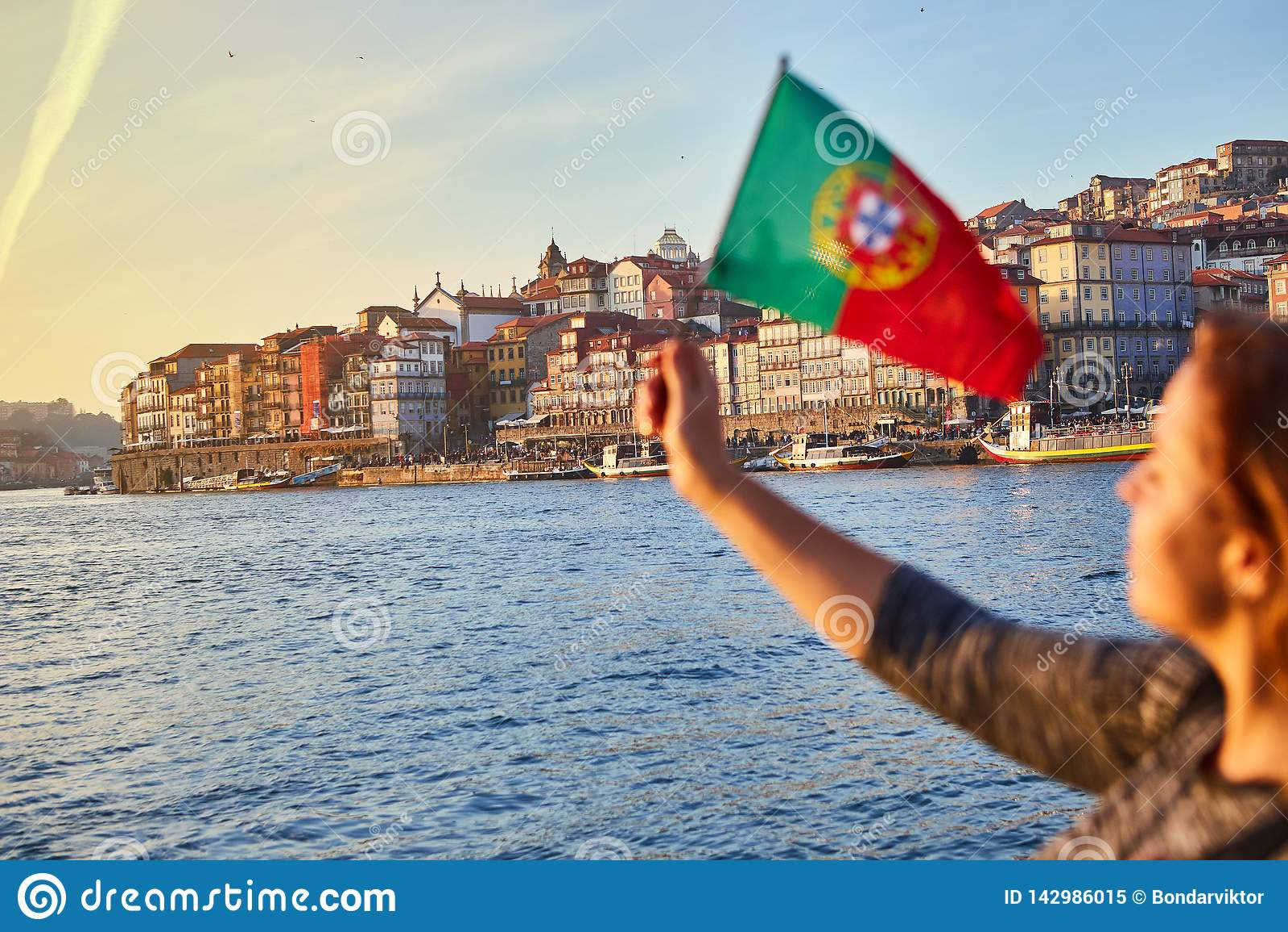 Turista da jovem mulher com bandeira portuguesa que aprecia a opinião bonita da paisagem no quarto e no rio históricos de Ribeira