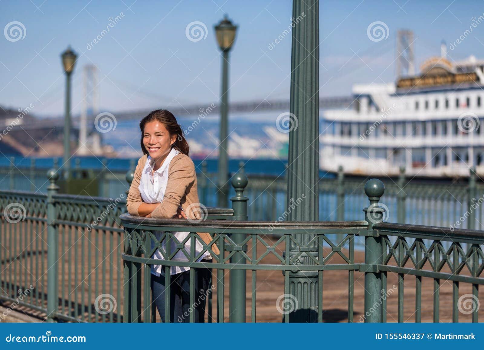Turista da menina do curso das férias do cruzeiro de San Francisco no cais do porto Mulher asiática que olha a vista do porto no