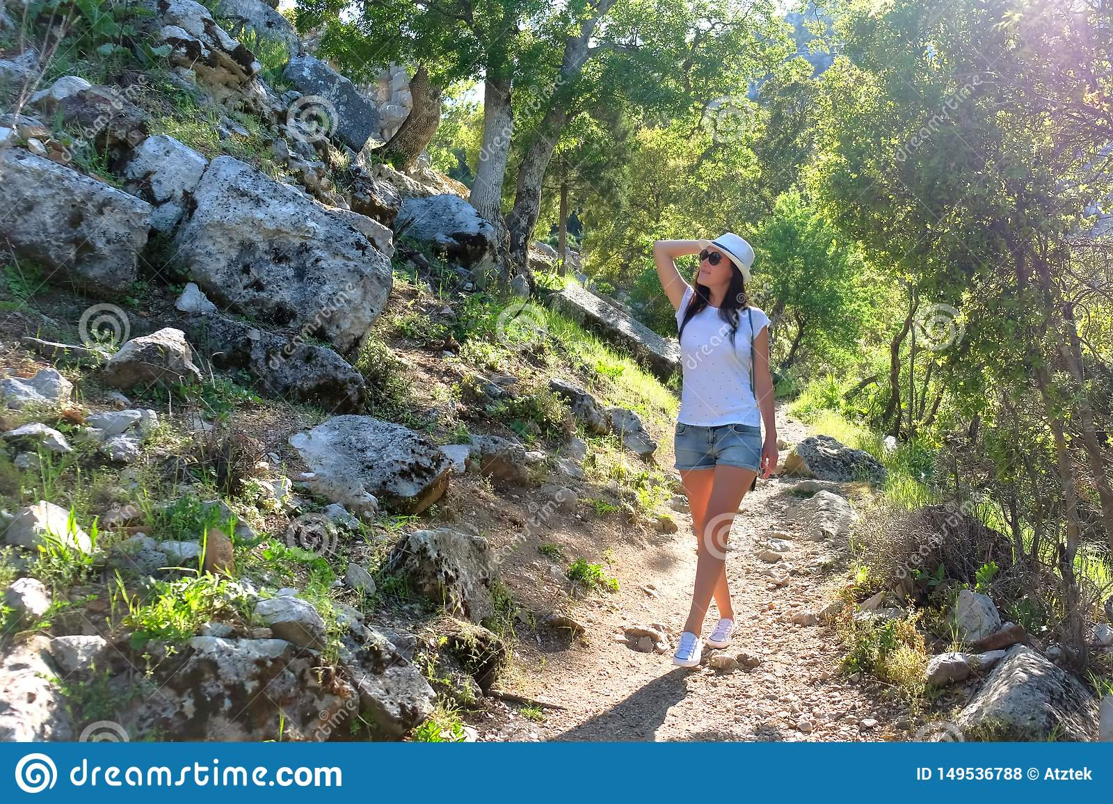 Turista da mo?a em um chap?u em uma caminhada em uma estrada de floresta da montanha, nas ru?nas da cidade antiga Termessos nos r