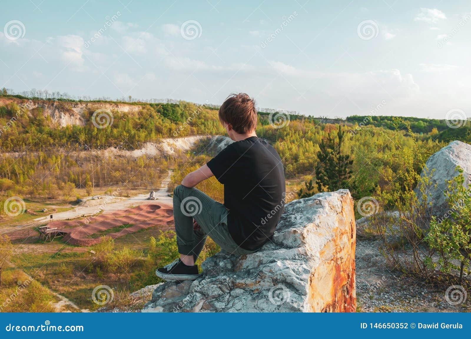 Turista del hombre joven que se sienta en la roca gigante, en el top de la montaña