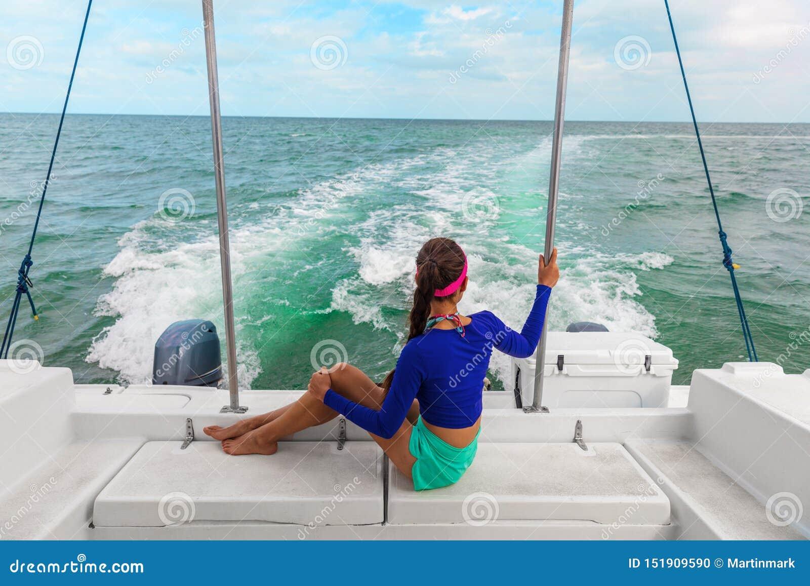 Turista della donna di giro di escursione della barca di viaggio che si rilassa sulla piattaforma del catamarano del motoscafo, F