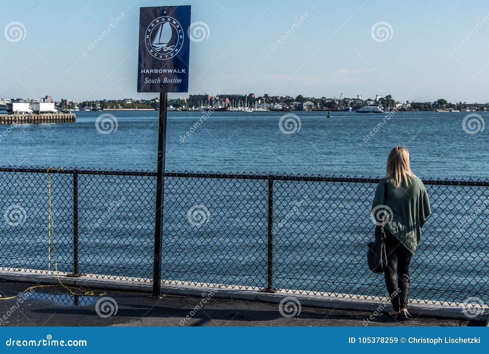 Turista della ragazza che sta la passeggiata vicina di panorama del porto di Boston del segno della posta isolata su un molo di l