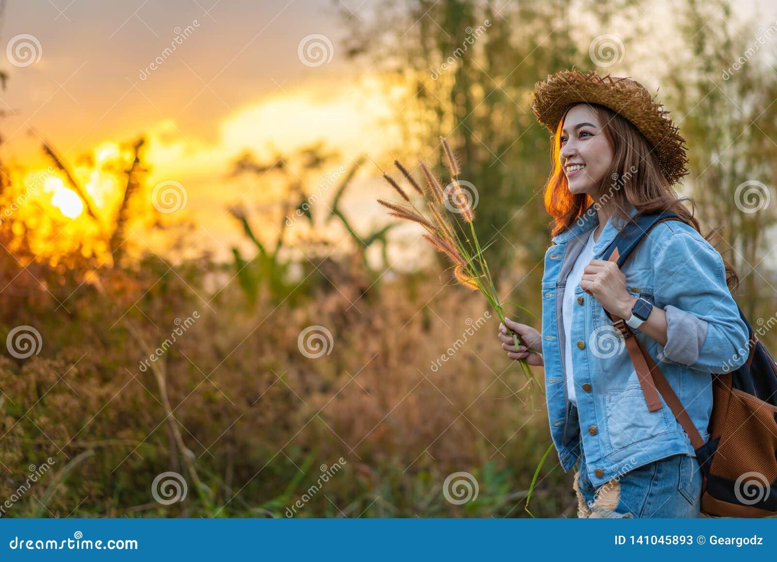 Turista fêmea com a trouxa no campo com por do sol