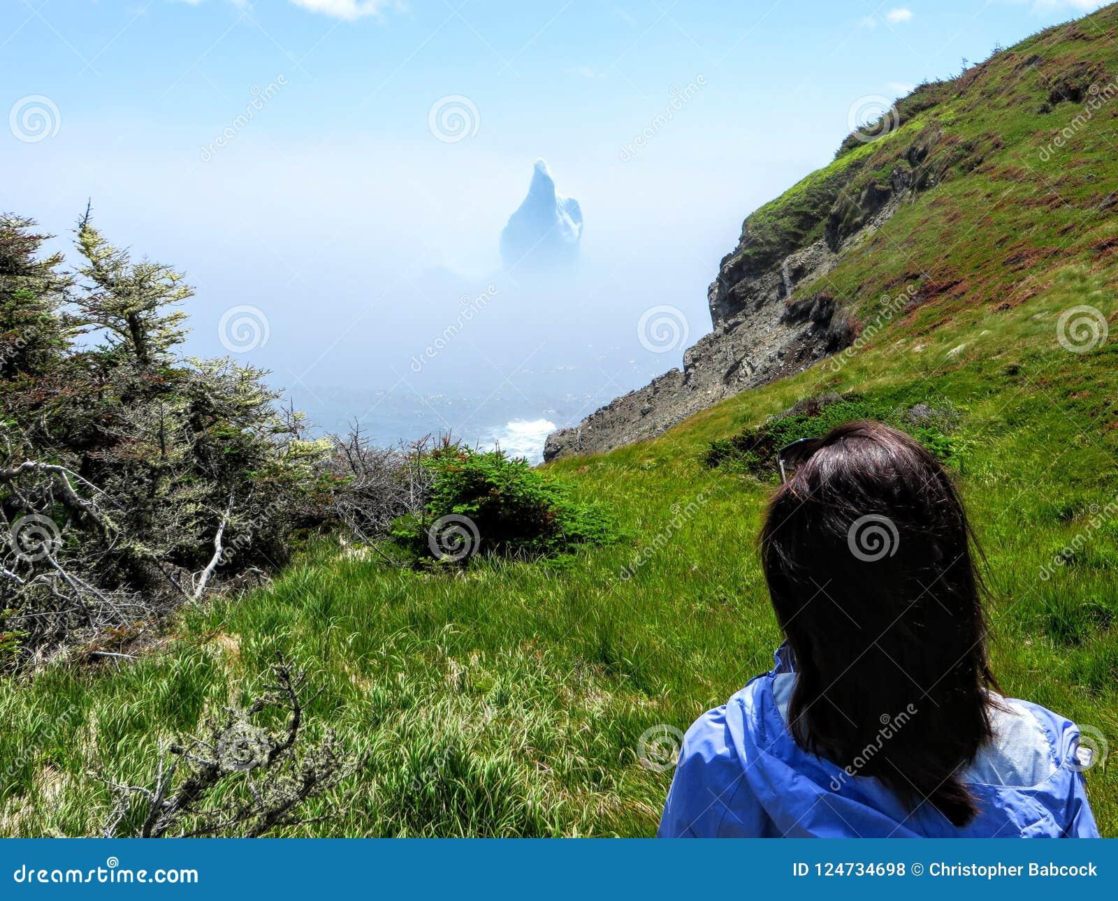 Turista fêmea que admira um iceberg incrível que flutua ao longo da costa áspera ao lado da fuga de Skerwink em Terra Nova e em L