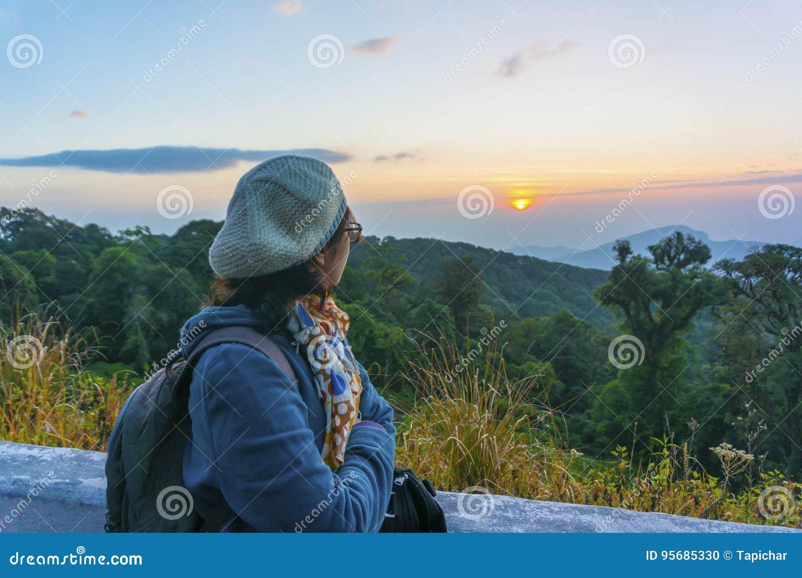 Turista fêmea que está e que olha a luz solar da manhã