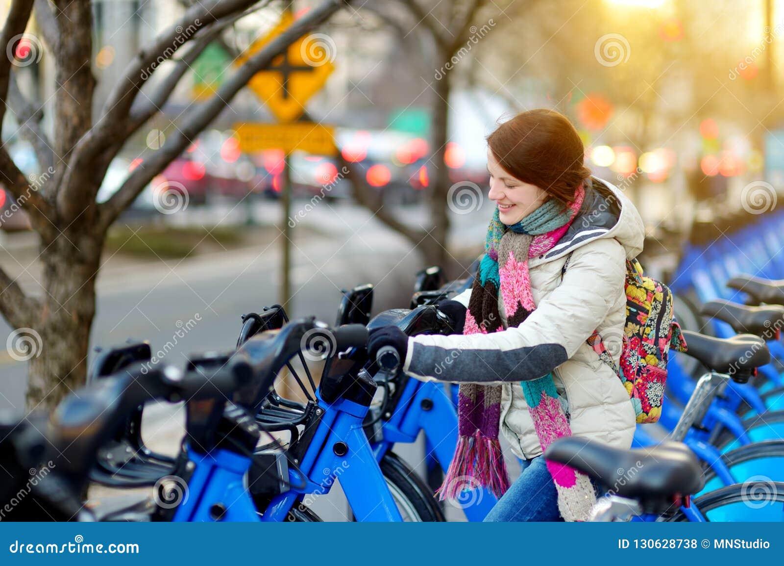Turista feliz da jovem mulher pronto para montar uma bicicleta alugado em New York City no dia de mola ensolarado Viajante fêmea