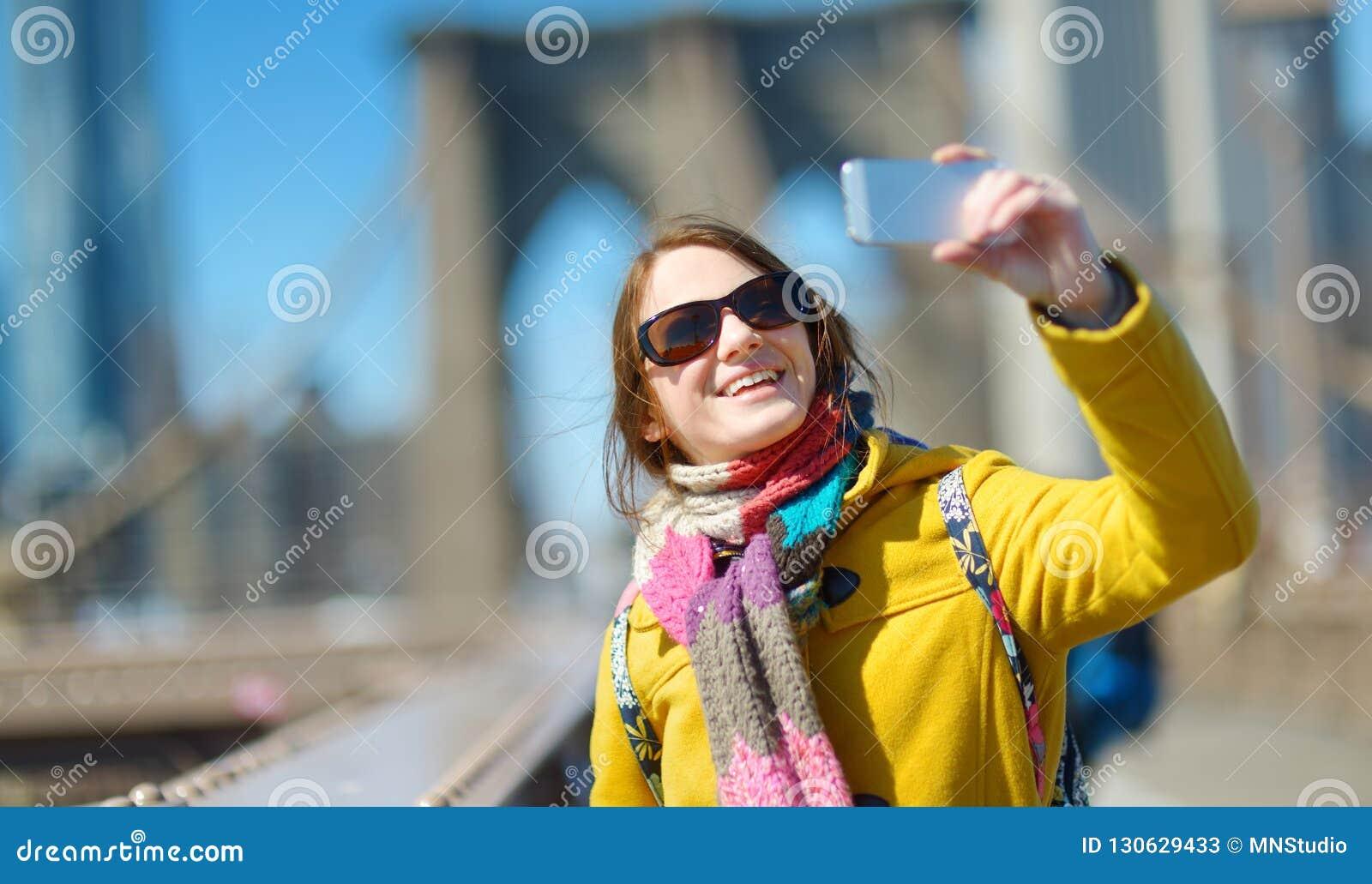bbca7987bb1 Turista feliz de la mujer joven que toma las fotos en el puente de  Brooklyn