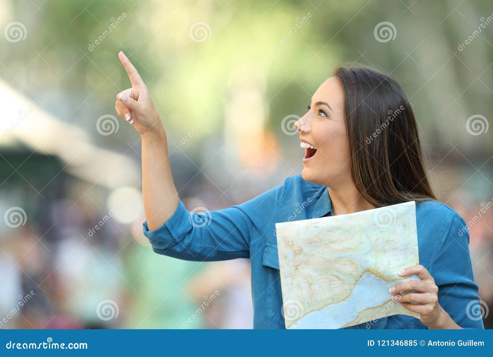Turista feliz que lleva a cabo a una guía que señala en el lado