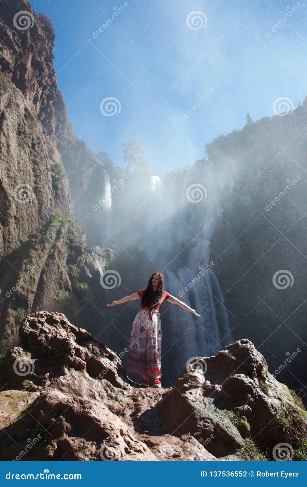 Turista femenino que presenta delante de la cascada