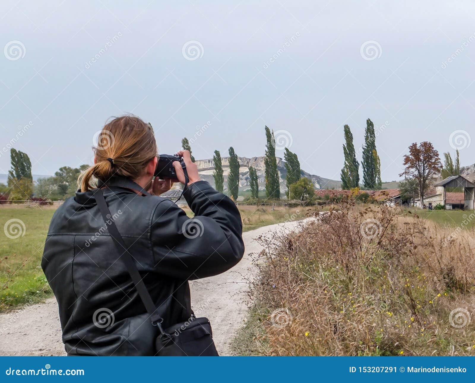 Turista joven en fotografías negras de la chaqueta de cuero el paisaje crimeo