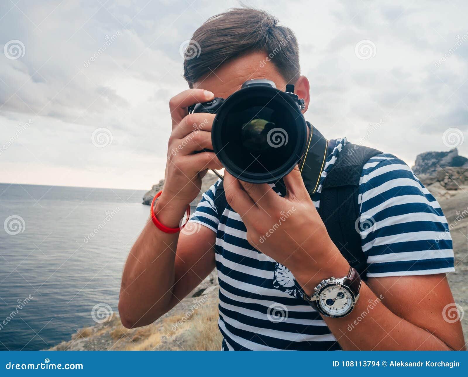 Turista masculino del fotógrafo con una cámara digital y una lente grande