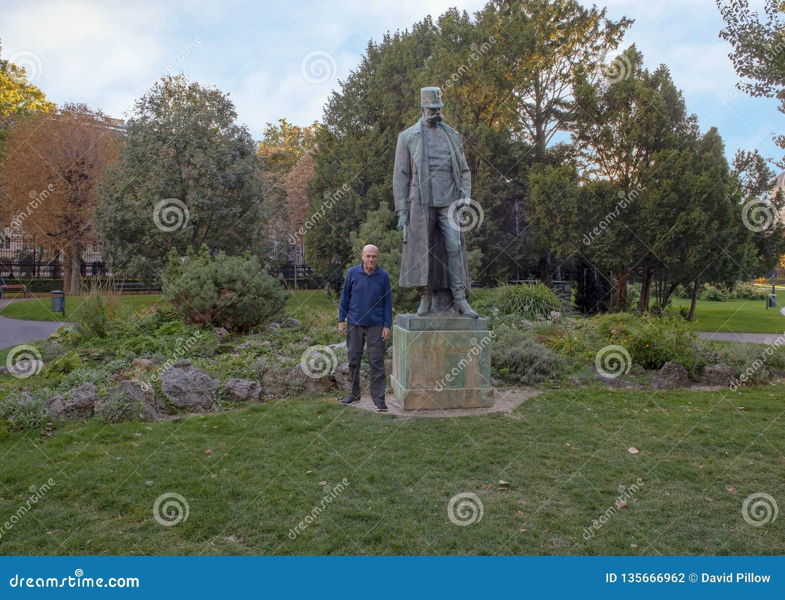 Turista pelo imperador de bronze Francis Joseph I da estátua de Áustria, parque de Burggarten, Viena