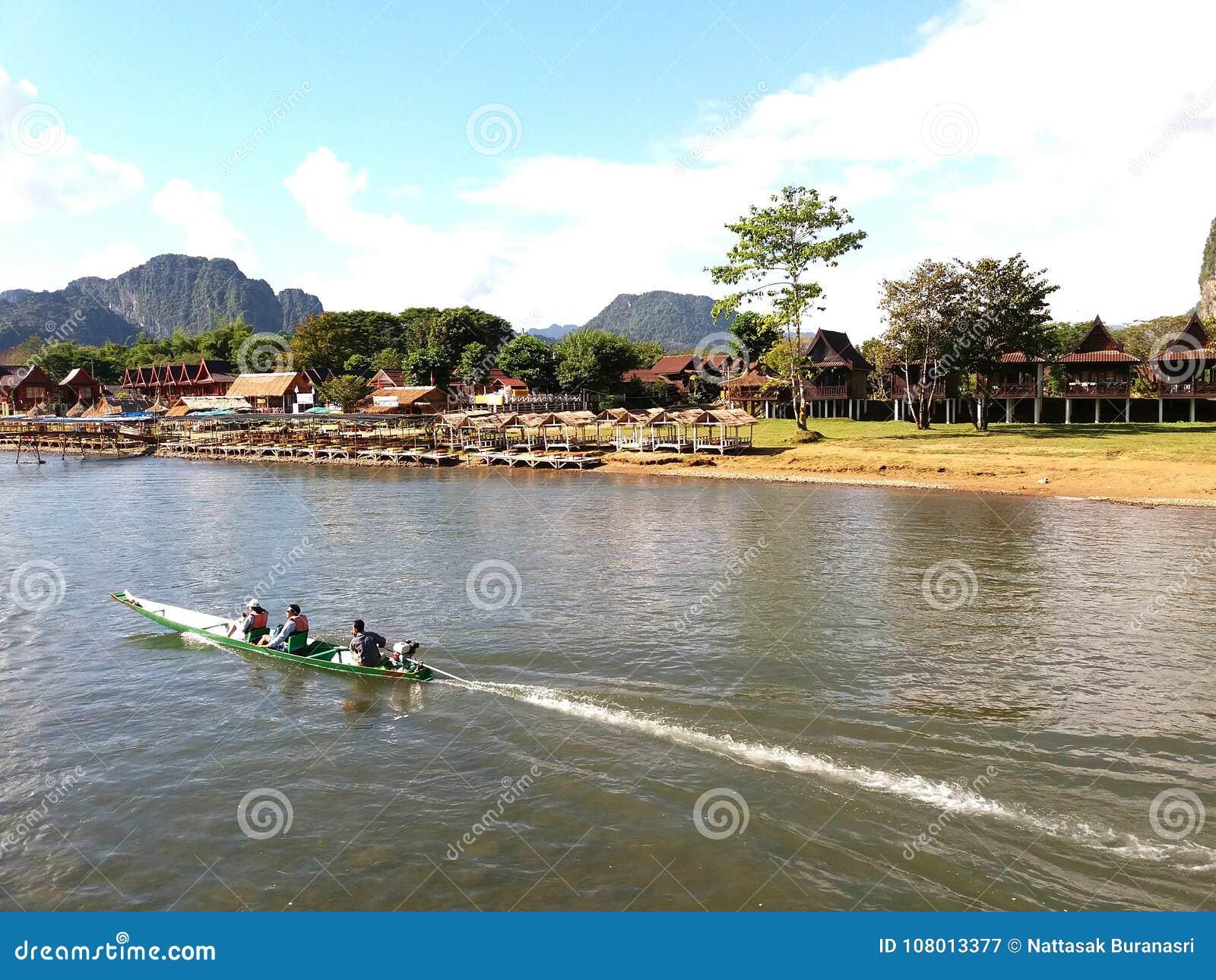 Turista que se sienta y que viaja en barco largo del rastro en el río y la montaña de visión, cielo azul con las nubes, orilla lo